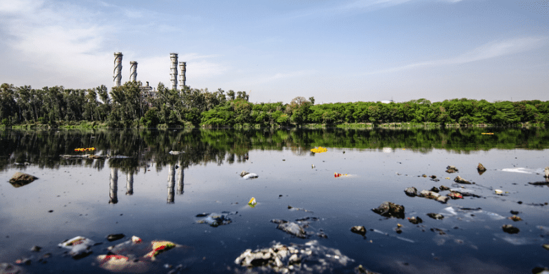 Plastic pollution floating in a lake with power plant towers in the background -Nat